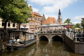 View on the canals of Alkmaar Netherlands with a boat cafe called Anna&Max and a cafe filled bridge