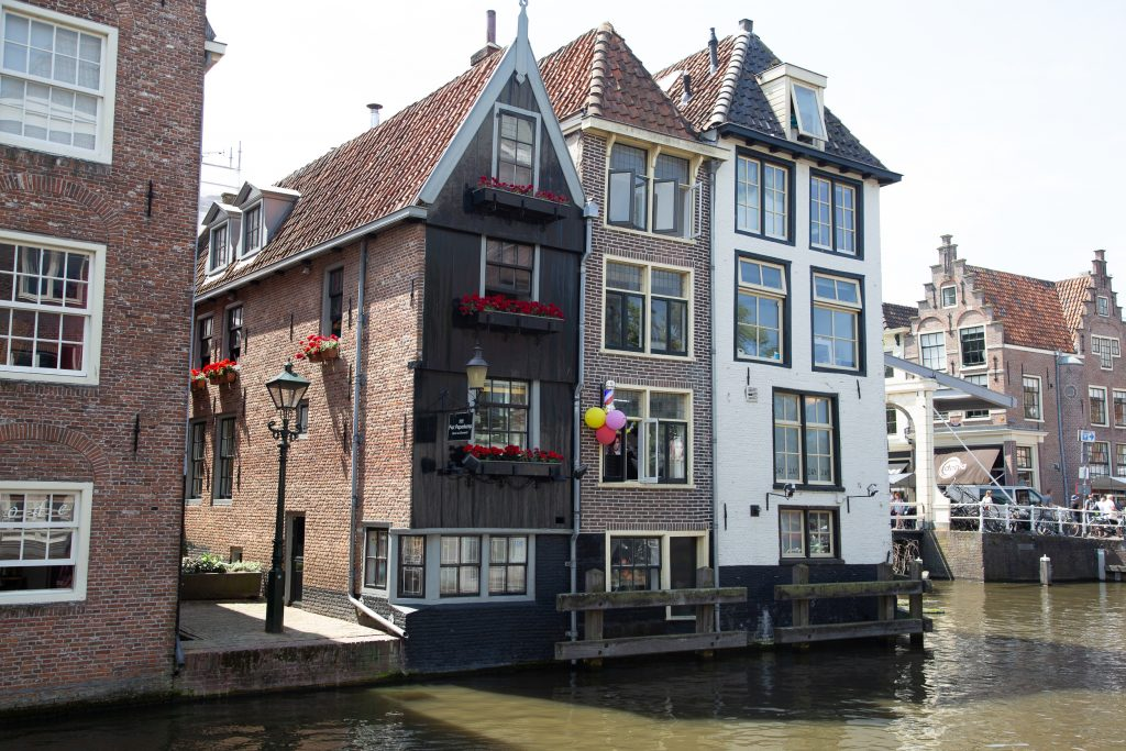 Three houses one of them with wooden panels, beautiful house fronts next to a canal in Alkmaar Netherlands