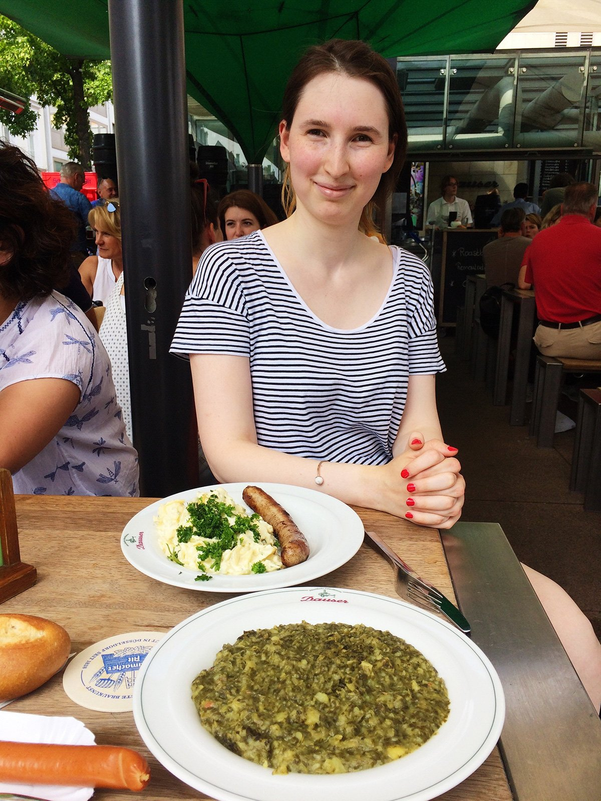 What to do in Dusseldorf Germany in a day: eat like a local. Girl in striped tshirt sitting before a table with plates filled with sausage