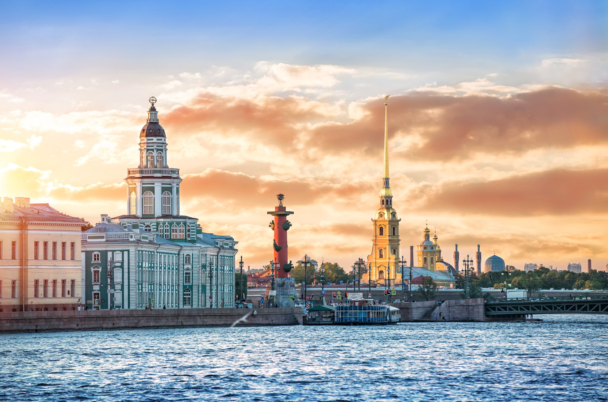 Kunstkammer, Rostral column, Peter and Paul Fortress and the Palace Bridge across the Neva River in St. Petersburg in the rays of the setting sun