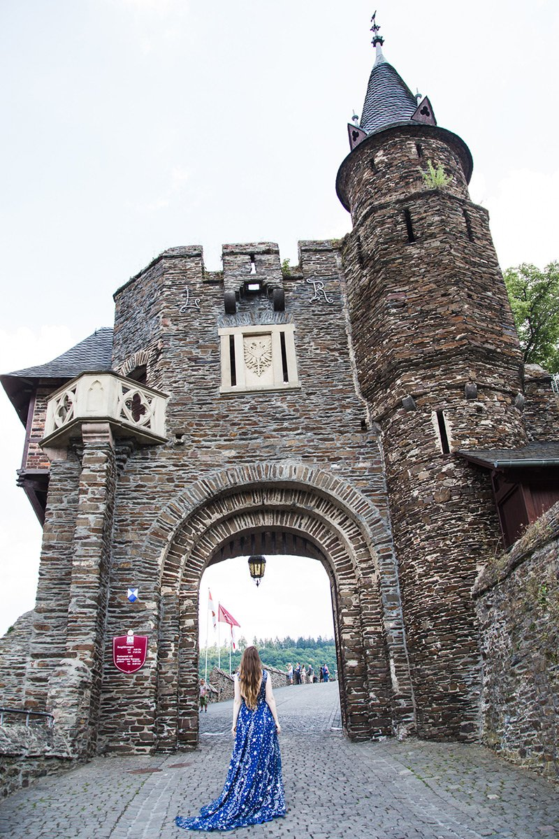 Cochem castle gates and girl in blue dress entering