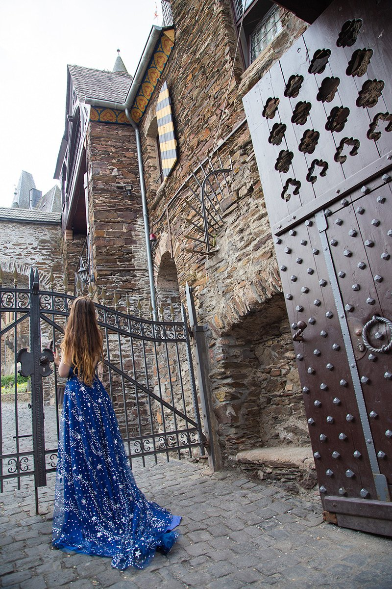 Girl in blue ball gown standing at castle gates