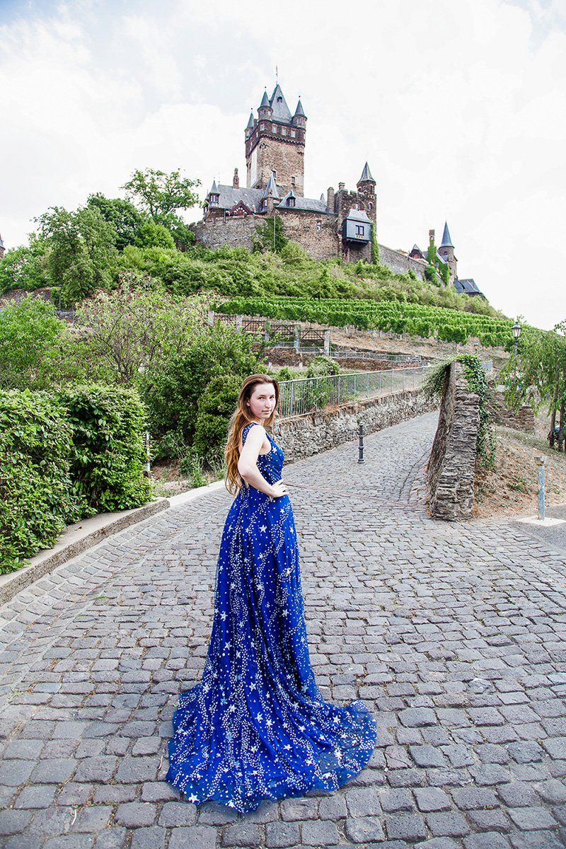 Cochem Castle in Germany with girl in blue ball gown standing in the front