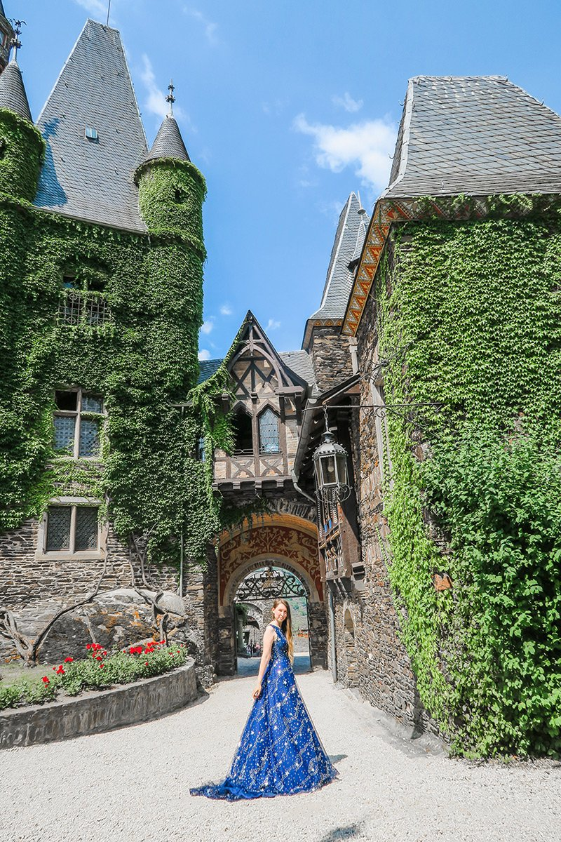 Girl in blue dress in the courtyard of Cochem Castle