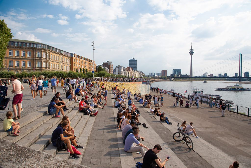 View on the Dusseldorf promenade with Rhein and the Rhein Tower visible in the distance with people sitting on the steps on a sunny day