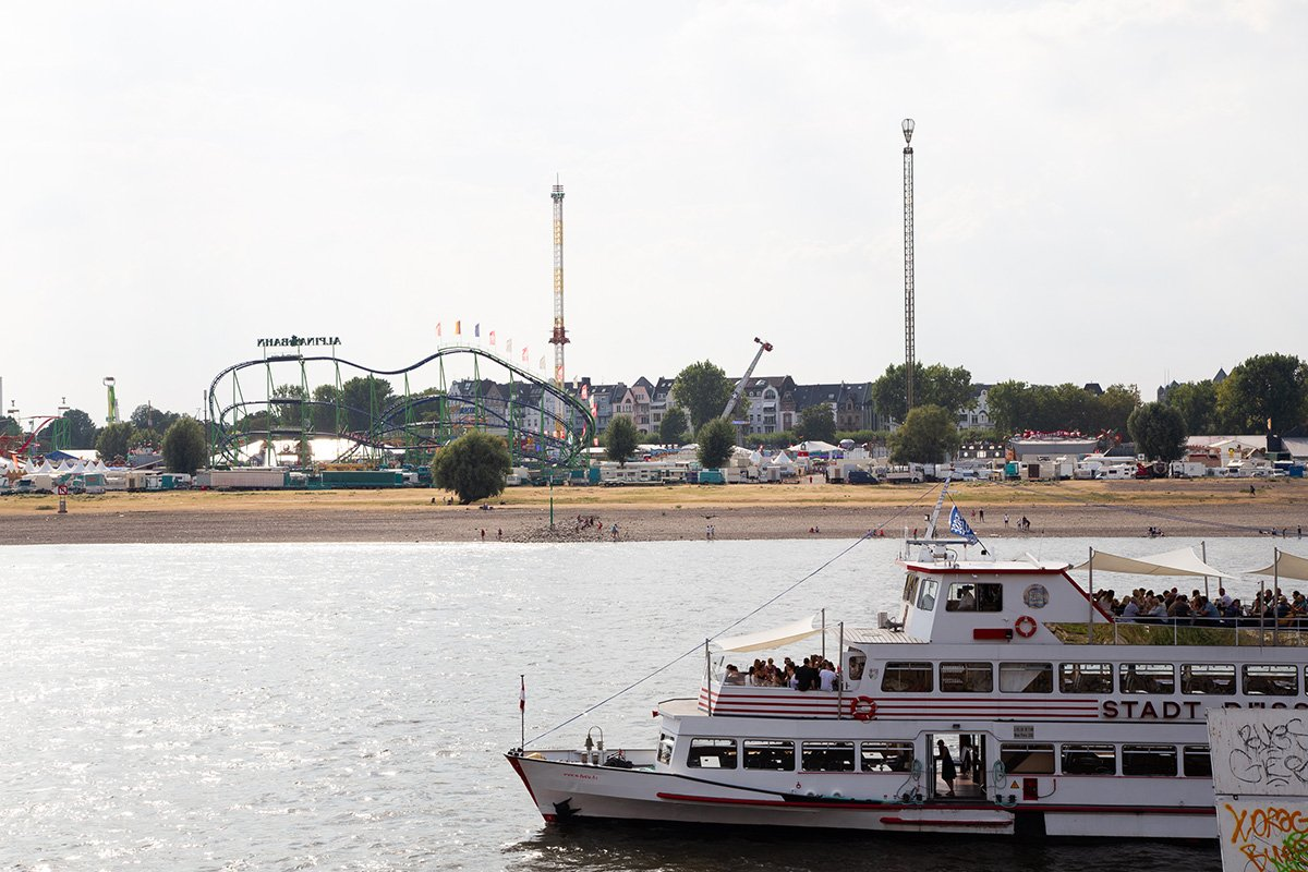 View of the Rhein river and the annual July fair in Dusseldorf, with a touristic boat passing in front