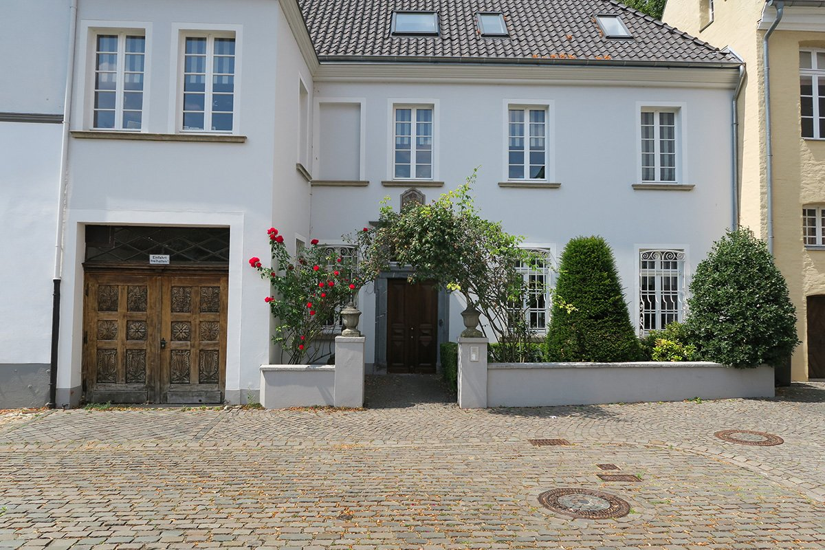 Beautiful house in Düsseldorf Kaiserswerth with a rose arch growing over the entrance