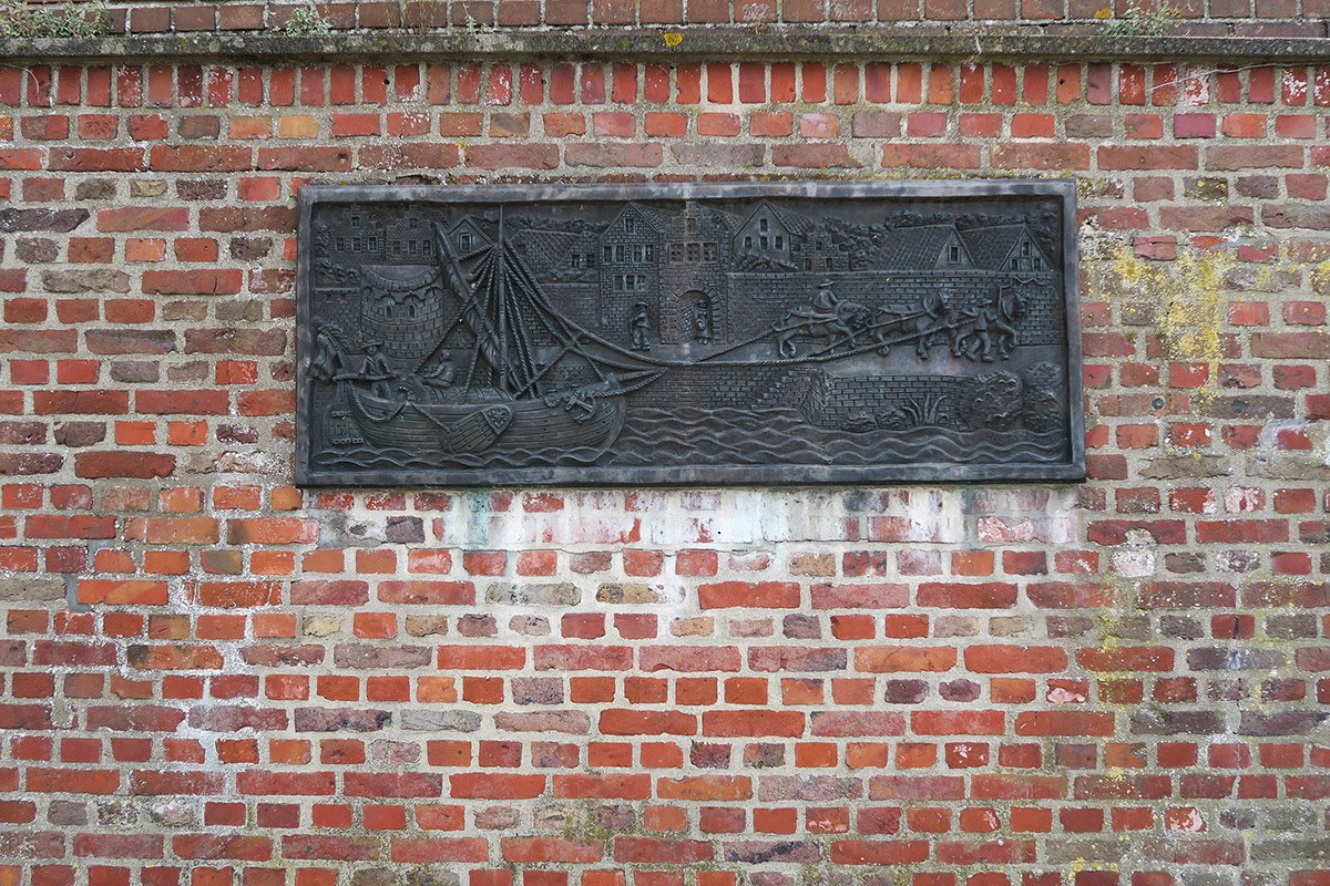 Brick wall with a tablet displaying a medieval scene of ships and horses