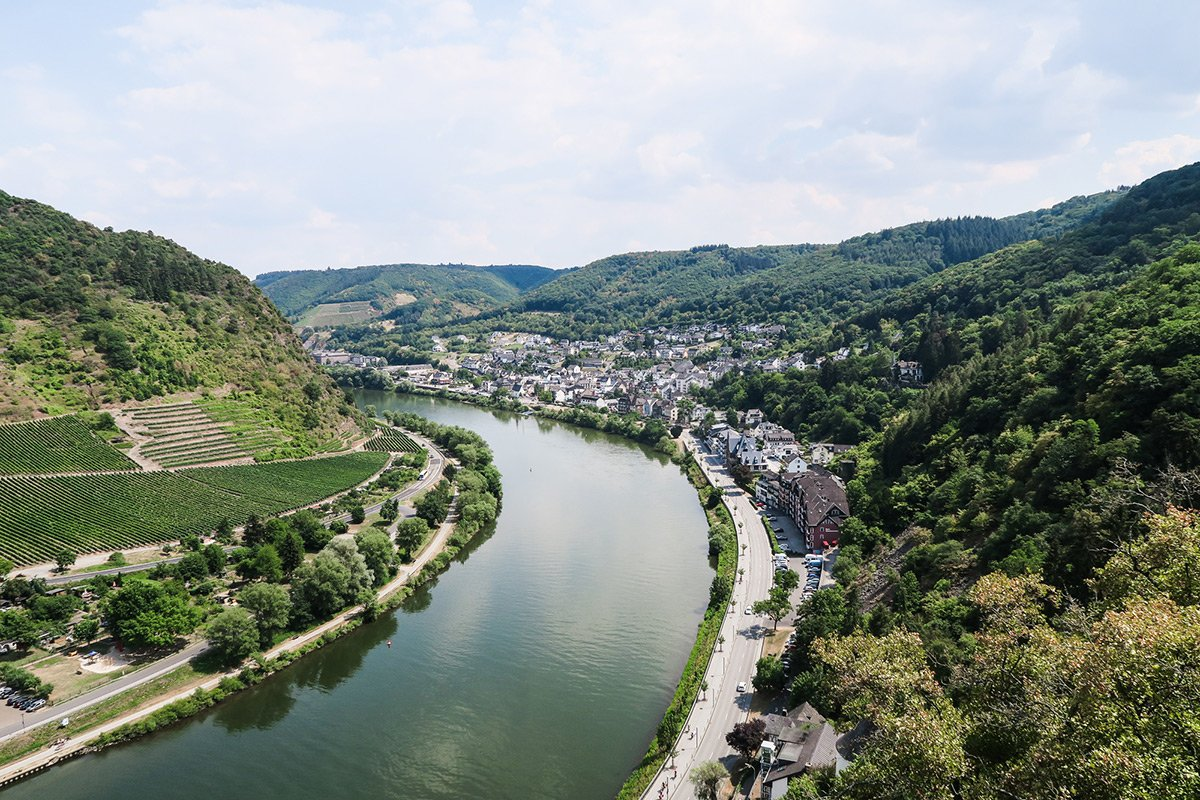 Mosel river with vineyards on one side and a village on the other