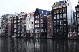 Canal houses in Amsterdam Damrak next to the water