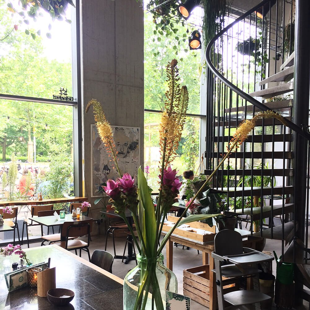 Restaurant decor in Benjis amsterdam with wide windows and spiral staircase